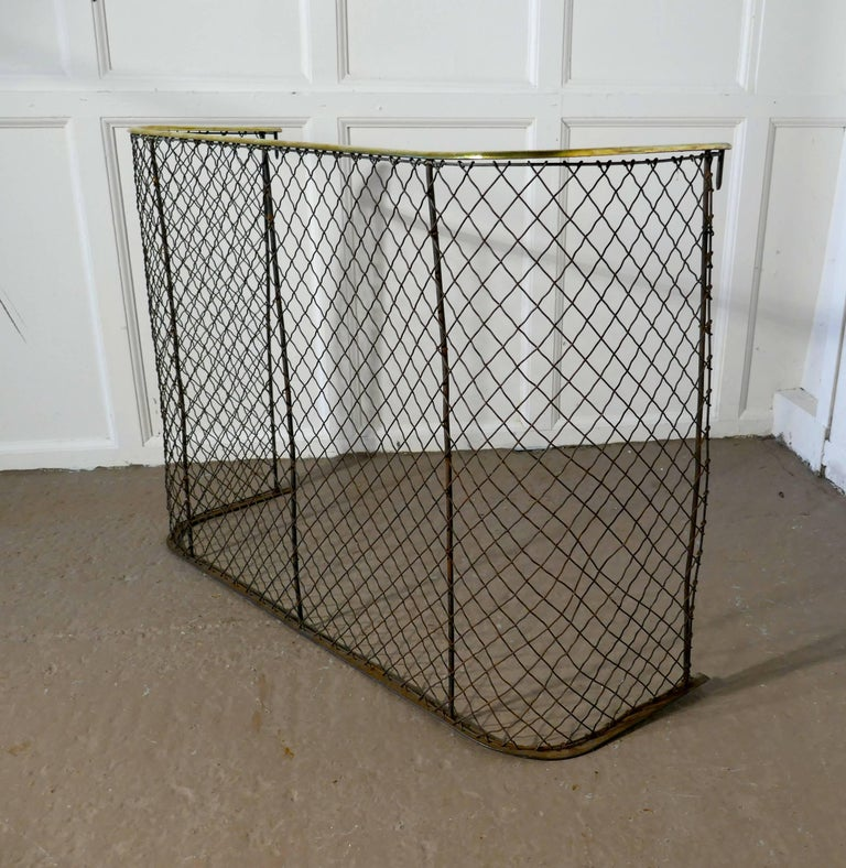 A Victorian nursery fire guard, brass fender  A high Victorian antique fire guard often known as a nursery guard as it completely surrounds the fire  The slightly curved brass topped rail is in very good order as is the wire chain mesh  Measure: