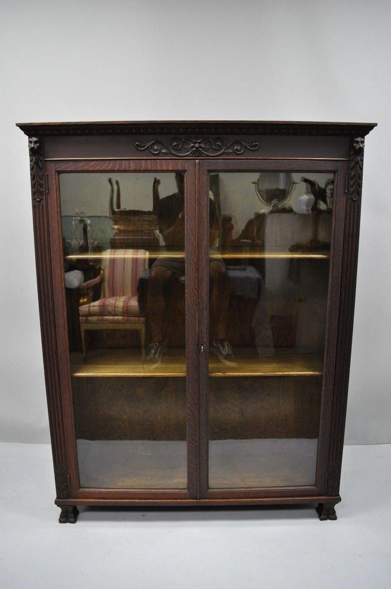 Antique oakwood Victorian glass two door bookcase with claw feet, carved lions, and northwind face. Item features carved claw feet, lion and northwind faces, beautiful wood grain, two glass swing doors, two adjustable wooden shelves, and working