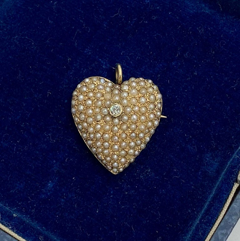 An Antique Victorian Heart Pendant set throughout with lovely Seed Pearls.  In the center is a sparkling Old Mine Cut Diamond.  The diamond and pearls are set in a wonderful 14 Karat Gold Heart.  The Heart has a swivel bale which can be flipped down