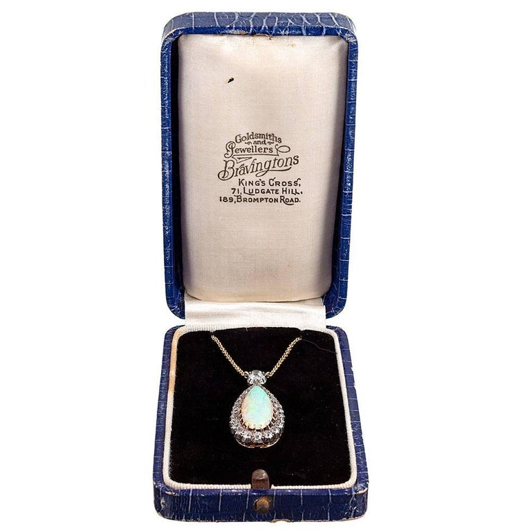 Ultra-fine Victorian pendant, made of silver over 18 karat yellow gold, the design centered upon an elongated pear cabochon opal that weighs approximately 6 carats and framed by a border of 2.00 carats of brilliant white diamonds. The pendant sits