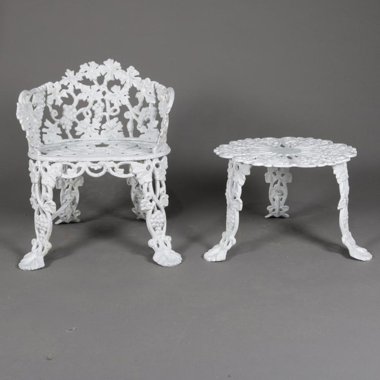 A 2 piece set includes a Victorian reticulated garden bench featuring cast iron construction in grape and leaf pattern and seated on cabriole legs terminating in stylized paw feet with matching garden table, painted white, 20th century  Measures: