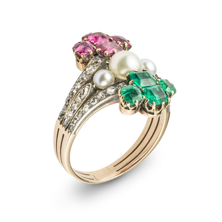 A mid nineteenth century emerald, ruby, diamond and bouton pearl ring, comprising a claw-set emerald quatrefoil surmounting three bouton pearls in a horizontal row and with a similar claw-set ruby quatrefoil below, all mounted in vertical alignment