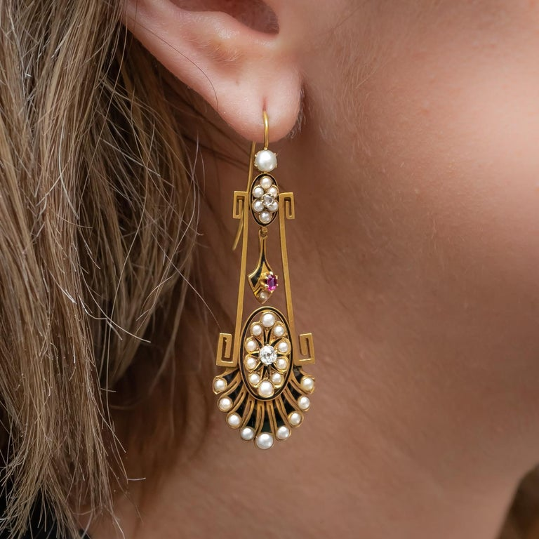 A pair of Victorian, aesthetic period, drop earrings, set with natural half seed pearls, old and rose-cut diamonds and rubies, with black enamel, mounted in gold, on hooks, circa 1875.