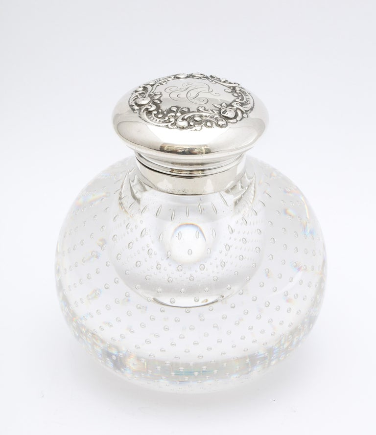 Victorian period, sterling silver-mounted controlled bubbles crystal inkwell with hinged lid, Gorham Mfg. Corp., Providence, Rhode Island, Ca. 1895. Interior of sterling silver hinged lid is lightly gilded; top of lid is decorated with flowers and