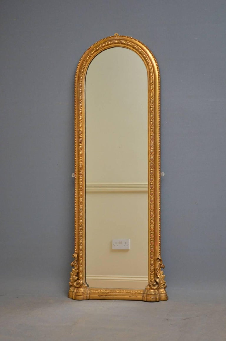 K0322 Victorian gilt pier mirror of unusually slim proportions, having original mirror plate with some foxing in finely decorated frame. This antique mirror has been refinished in the past and is in wonderful home ready condition, circa