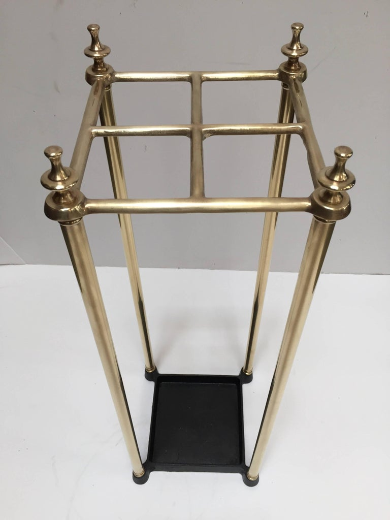 Victorian brass umbrella stand or stick stand. Polished brass top divided into four sections to hold either walking sticks or umbrellas. Square umbrella brass valet rack with four sections and black iron tray and supported upon a tubular frame