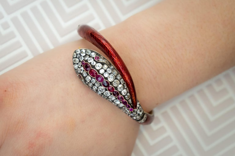Victorian red guilloche enamel snake bangle, the head is set with old-cut diamonds and rubies with red enamel set to the body and tail, with diamond detail to the three hinges. Circa 1860.