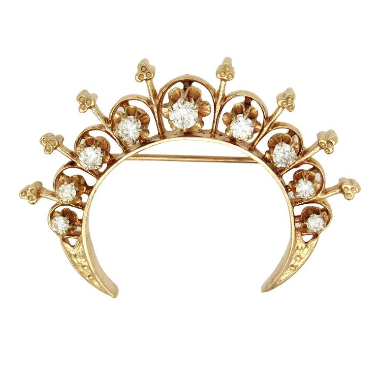 Victorian Revival diamond crescent pin, circa 1940's, is set with 9 diamonds, approx. 1 carat tw, in 14K gold.. The brooch measures 2