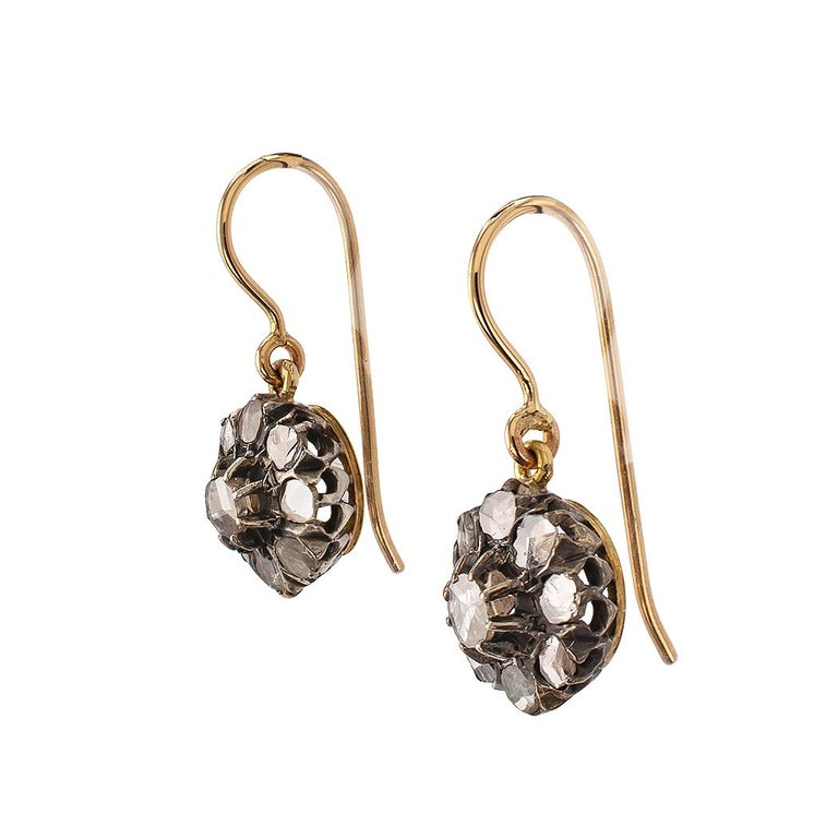 Victorian rose cut diamond gold and silver drop earrings circa 1890. The circular designs set throughout with rose cut diamonds totaling approximately 0.70 carat, mounted in silver and 14-karat yellow gold. Very pristine condition consistent with