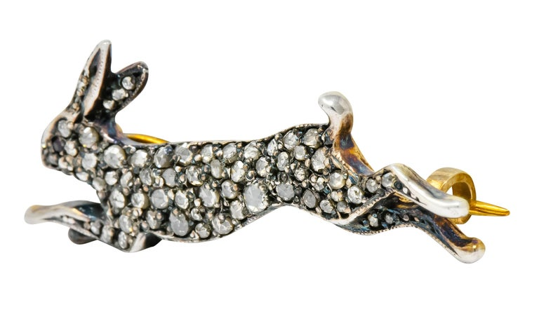 Brooch designed as a silver topped hare, mid leap, bead set throughout by rose cut diamonds  Accented by round cut ruby eye and some milgrain detail  Completed by pin stem and closure  Tested as silver-topped 10 karat gold  Measures: 5/8 x 1 5/8