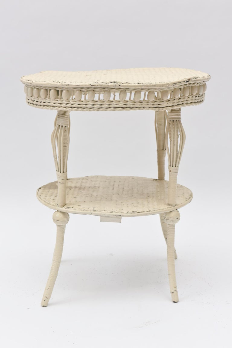 This 1898 wicker table is an excellent example of Heywood Bother's and Wakefield Company Victorian Era. It features a combination of an apron using wooden beads as well as birdcage splayed legs, all elements of a fine Victorian piece with a second