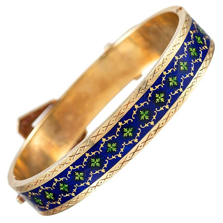 Buckle motif jewelry was popularized by Queen Victoria, as she was known to favor this theme. This 18 karat yellow gold bangle is extensively decorated with royal blue and Kelly green enamel and further complimented with seed pearls. The interior
