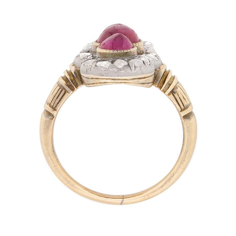 This quintessential Victorian era beauty features a vertically-arranged trio of rubies outlined by a grain set border of 0.24ct rose cut diamonds.  The gemstones, which feature a ruby cabochon at centre flanked by oval cuts, are set in platinum and