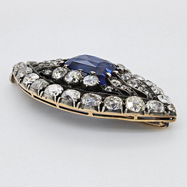 A Victorian sapphire and diamond brooch, ca. 1880s.   The brooch is designed in the form of an eye. Hereby the iris is set with a cushion shaped sapphire, weighing circa 9 carats. It is of Ceylon origin and natural (not heated), with a beautiful