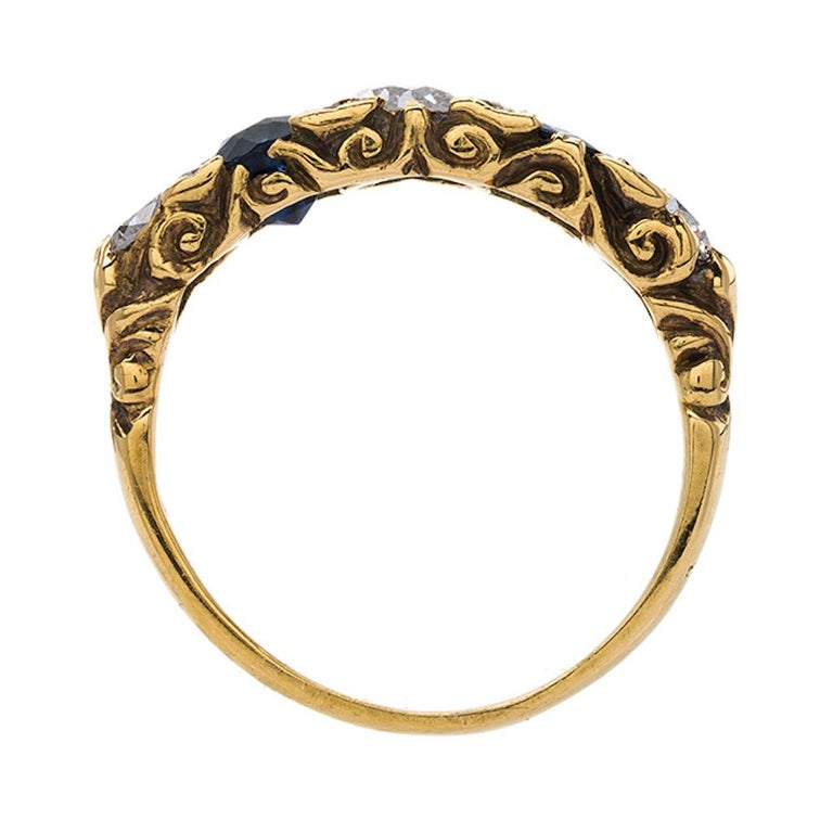 This is a charming and authentic Late Victorian era (circa 1900) 18k yellow gold ring featuring a winning sapphire and diamond combination. The ring centers three Old European Cut diamonds that total approximately 0.55ct in weight and graded H-J