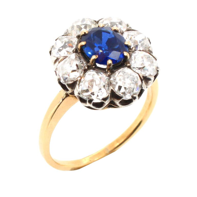 An antique Victorian sapphire and diamond cluster ring, ca. 1880s. The central cushion shaped sapphire weighs circa 1.5 carats and is a natural, not heat treated, gemstone -  accompanied by a gemological certificate. It is surround by a diamond