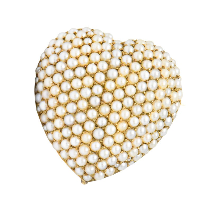 Featuring a puffed heart set with seed pearls in various hues of white and off-white  With fold-down bail, pin stem and hook to add a drop  Measuring 1 1/4 Inches (with bail)  Victorian Era  Width: 1 Inch  Total Weight: 5.9 Grams  Lovely. Romantic.