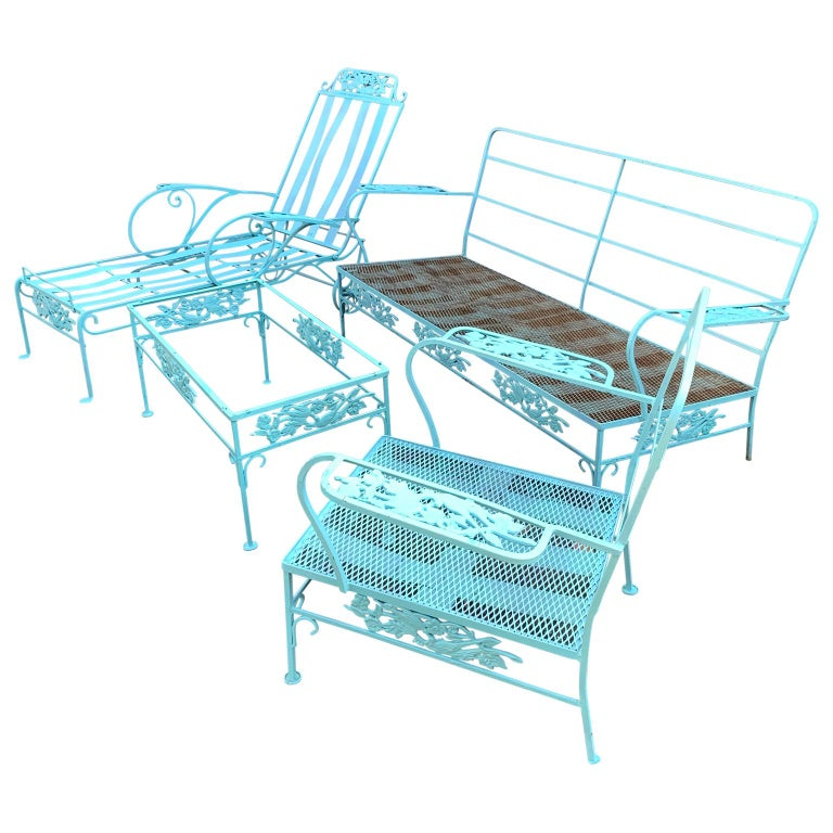 Turquoise painted iron garden patio cocktail table, lounge chair, two person sofa and armchair. This late Victorian set is featuring scrolled iron corners that conjoin and taper ending with flat round feet. The frieze is decorated with birds and