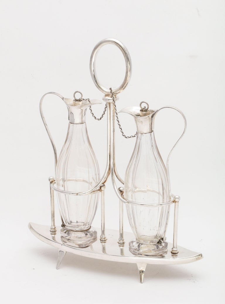 Victorian, Sheffield plated, footed, two bottle cruet set (consisting of the two bottles, stoppers and stand), Sheffield, England, circa 1878, William Hutton and Sons - makers. Stand measures: 10 1/8 inches high (to top of handle) x 8 1/2 inches
