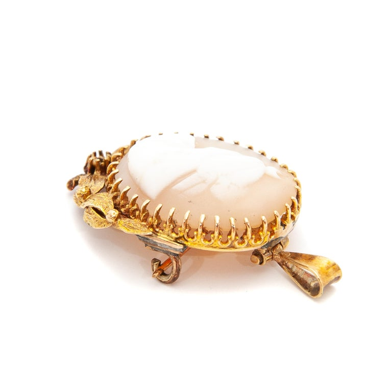 Gorgeous oval-shaped cameo shell brooch with a cutout of a female silhouette. The carved shell is set in 14 karat yellow gold with a gold floral border and leaf design. This cameo can be worn as a brooch and pendant.  The pendant brooch is in good