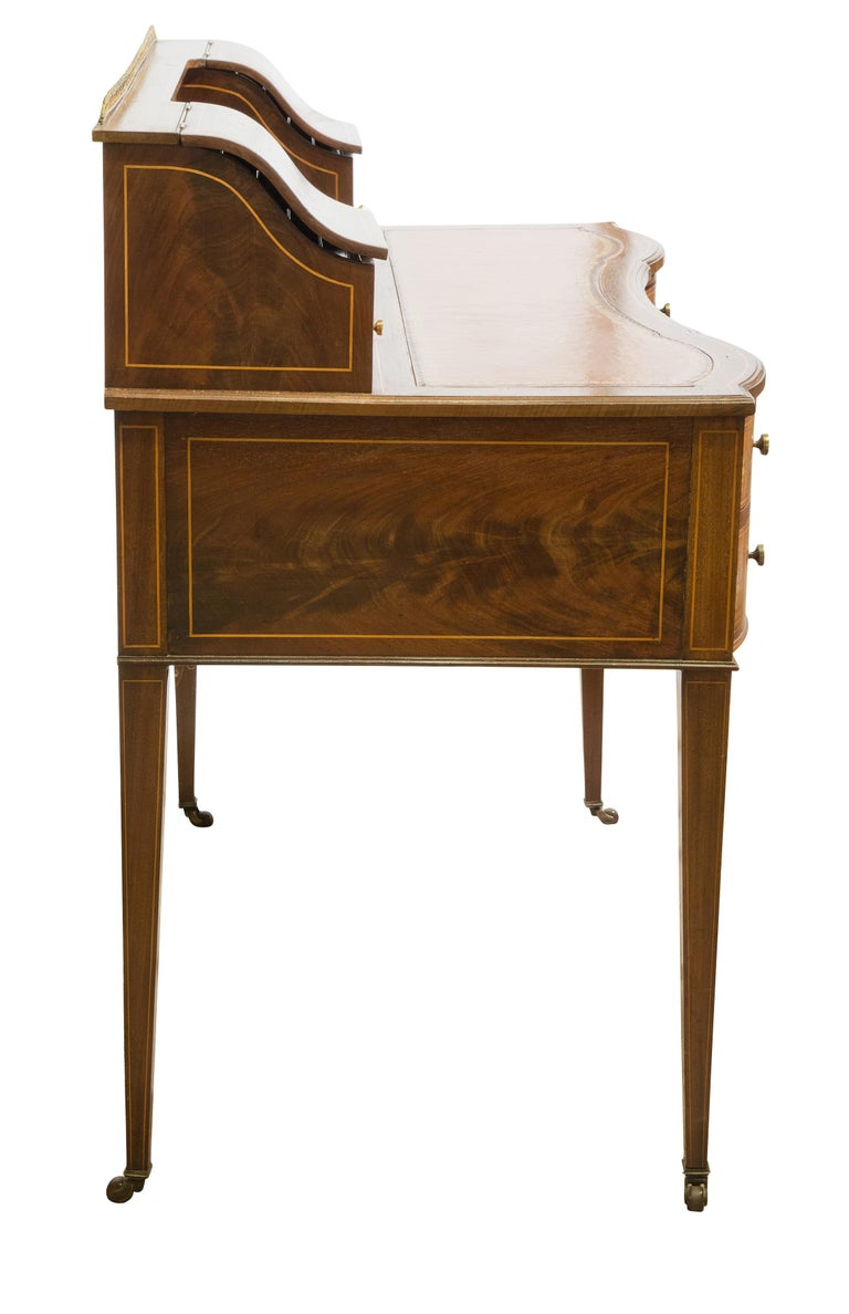 A late Victorian Sheraton revival mahogany Bonheur du Jour, marquetry inlay, leather top, inverted serpentine front with five drawers, brass locks and knob handles, on square tapering legs.