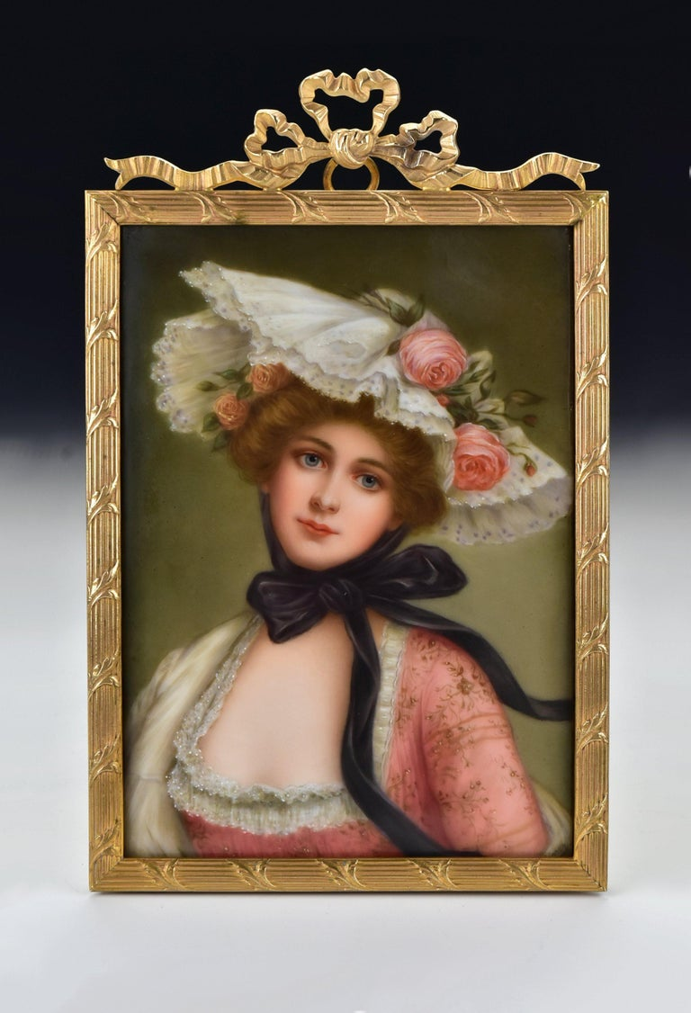 Description: Hand painted portrait on porcelain depicting a young woman with a large hat, artist signed Wagner on the front and marked on the back as shown, set in a fancy bronze frame.  Age: Late 19th century  Size: The painting alone measures