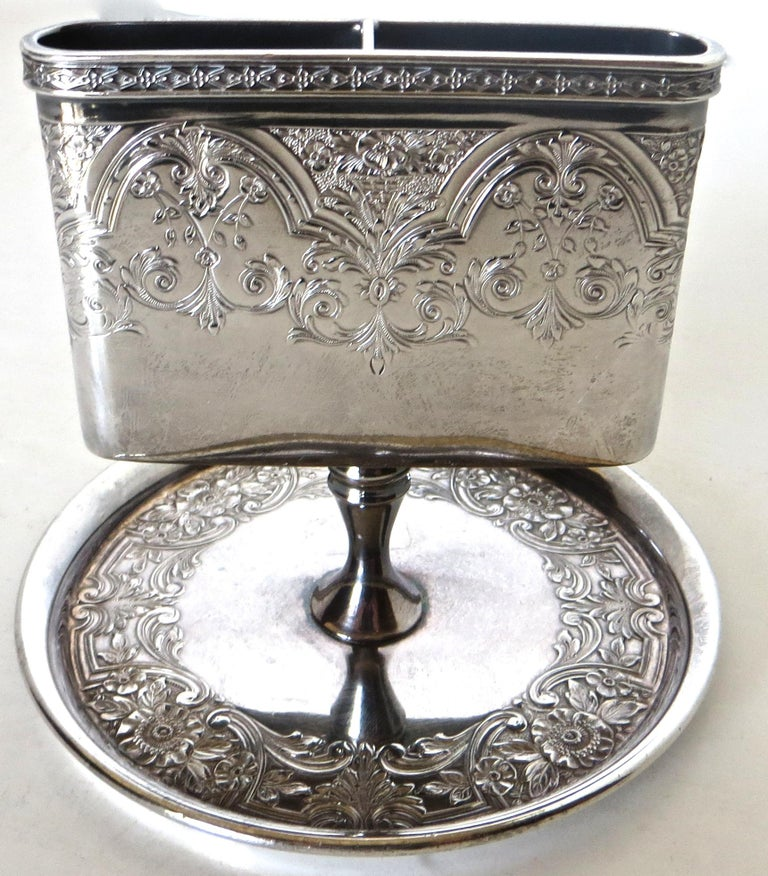 This Victorian match holder is highly decorated with etched floral design to both sides and wrapped completely around of the holder. An even more elaborate detailed etched floral pattern is applied to the waste receptacle circular dish below. The