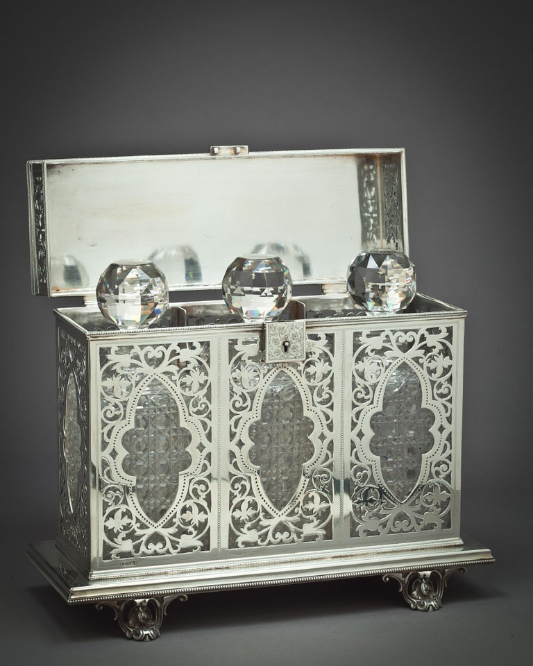 A Victorian silver Tantalus with three cut glass decanters and stoppers. The Tantalus is marked Sheffield, 1896, probably Harrison brothers and Howson.