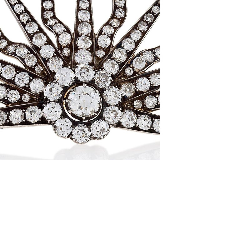 An Antique silver top/gold brooch with diamonds. The brooch has 1 old European-cut diamond with an approximate total weight of 0.75 carats, 10 old European-cut diamonds with an approximate total weight of 1.50 carats, and 139 old mine-cut and rose