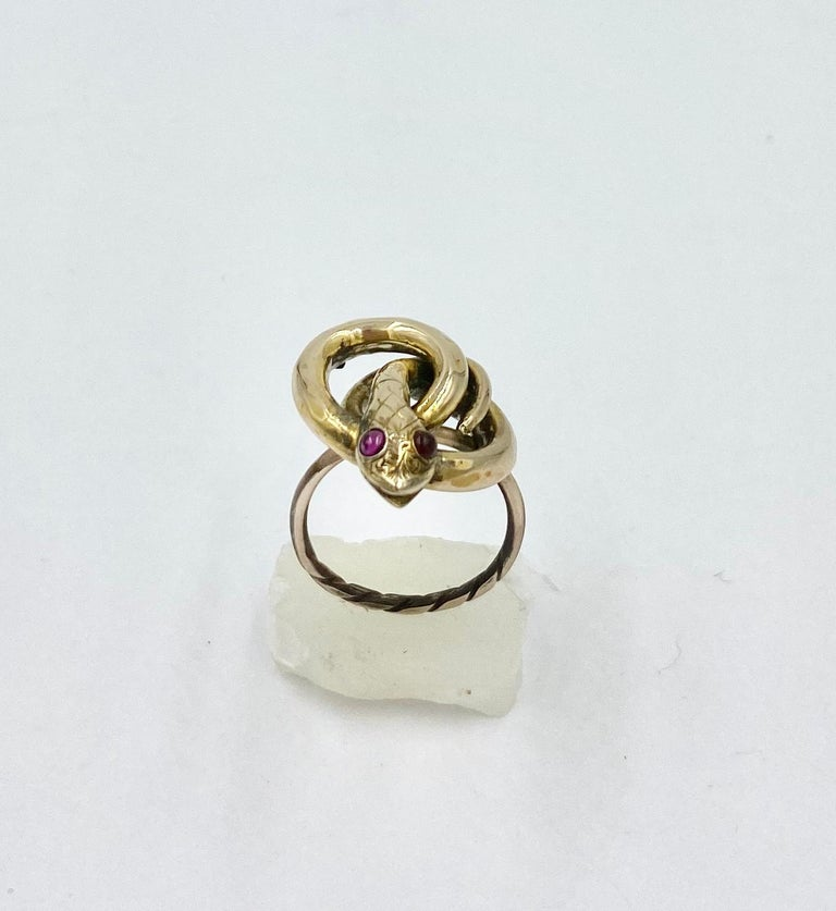 A rare and wonderful antique Victorian Snake Ring with two Bohemian Garnet Eyes in 10 Karat Gold.  The stunning fully modeled three dimensional snake is depicted coiled around itself and raising its glorious head.  The wonderful head has an open