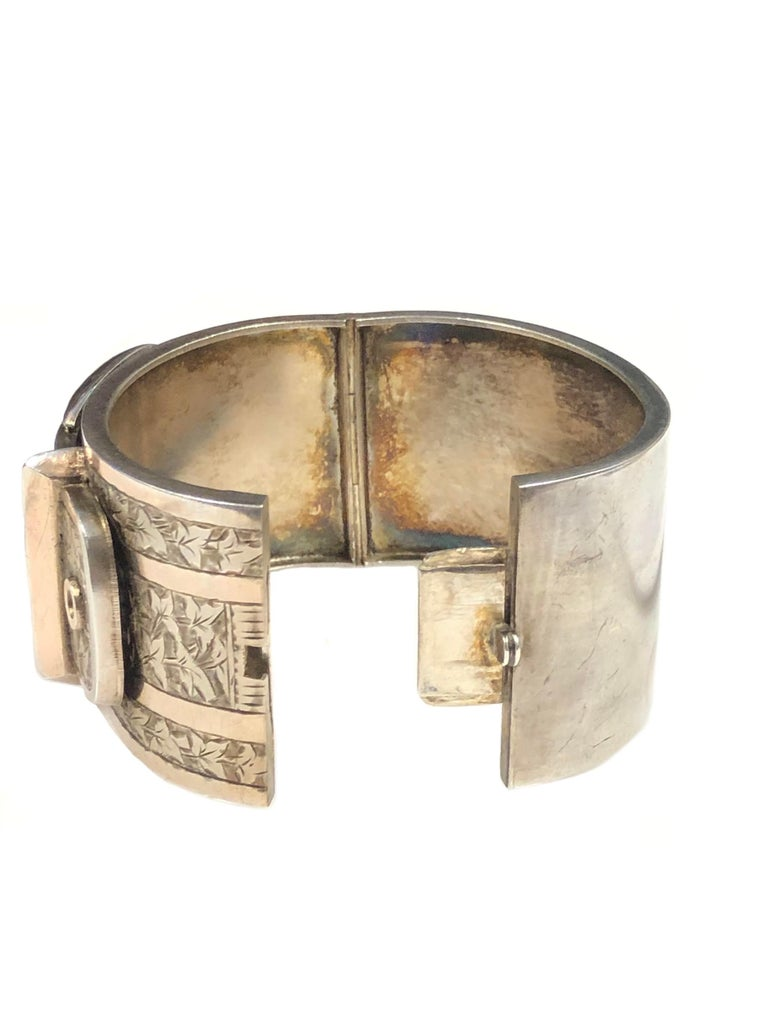 Circa 1908 Hardy Brothers of Birmingham England Sterling Silver Bangle Bracelet, measuring 1 1/2 inches wide and having a Buckle Motif on the top and finished with Hand Engraved design work and a snap closure, Wrist size 7 inches.