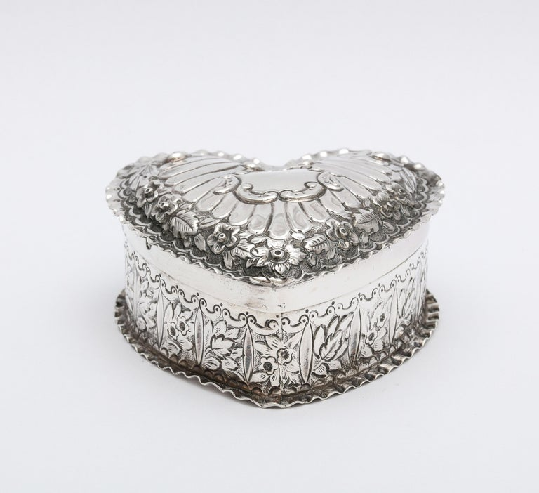 Victorian, sterling silver heart-form trinkets box with hinged lid, Birmingham, England, 1890, T. Hayes - maker. Gilded interior. Measures 2 3/4 inches deep x 2 3/4 inches wide (at widest point) x 1 1/4 inches high. Weighs 1.940 troy ounces. Vacant