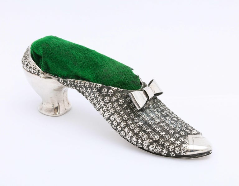 Victorian, sterling silver, high-heeled shoe-form pincushion, Birmingham, England, year-hallmarked for 1888, Adie and Lovekin - makers. Shoe is also marked sterling. Measures 4 3/4 inches wide x 1 1/4 inches deep x 1 3/4 inches high at highest