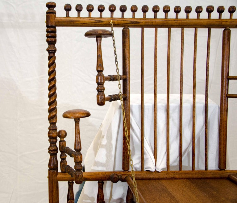 This unusual Victorian wall hanging oak hat and coat rack has five movable parts. There are four hat stands that can adjust away from the wall depending on the size of the hat. They are located on both sides of the drop-down center shelf. The center