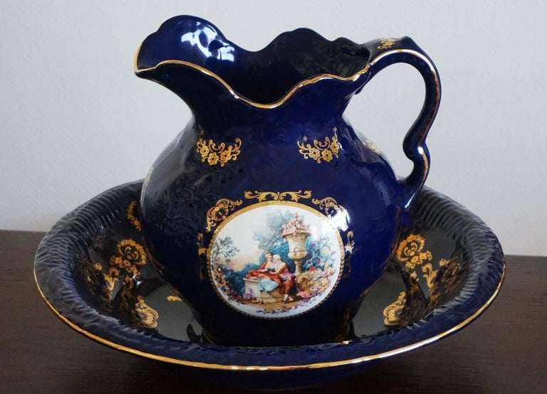 Beautiful Victorian style cobalt blue porcelain wash bowl and pitcher, Portugal 20th century. Hand painted courting scene at both sides and gilded decor, marked.