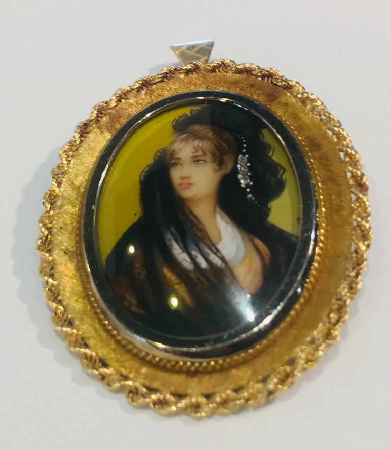 Lovely oval shaped pendant or brooch has a hand painted miniature painting of a beautiful young woman with 3 diamonds accenting her veil.  Painting is protected with a white gold, bezel set crystal, with a frame of 18 karat yellow gold Florentine