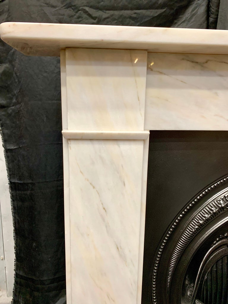 A handsome period Victorian style lightly veined statuary marble fireplace surround of simple form. A square shelf sits above a plain frieze, flanked by stepped jambs with splayed separation moulding to lower frieze line, all resting on moulded foot