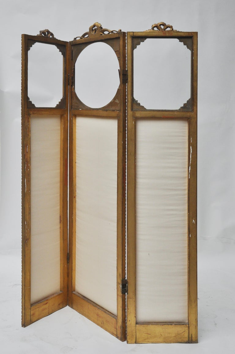 Victorian screen has hinges that bend in both directions. The fabric is off-white. The top of each panel has a piece of glass so that you can see through the top of the screen. The tops wooden pieces are carved and fragile. The middle panel is