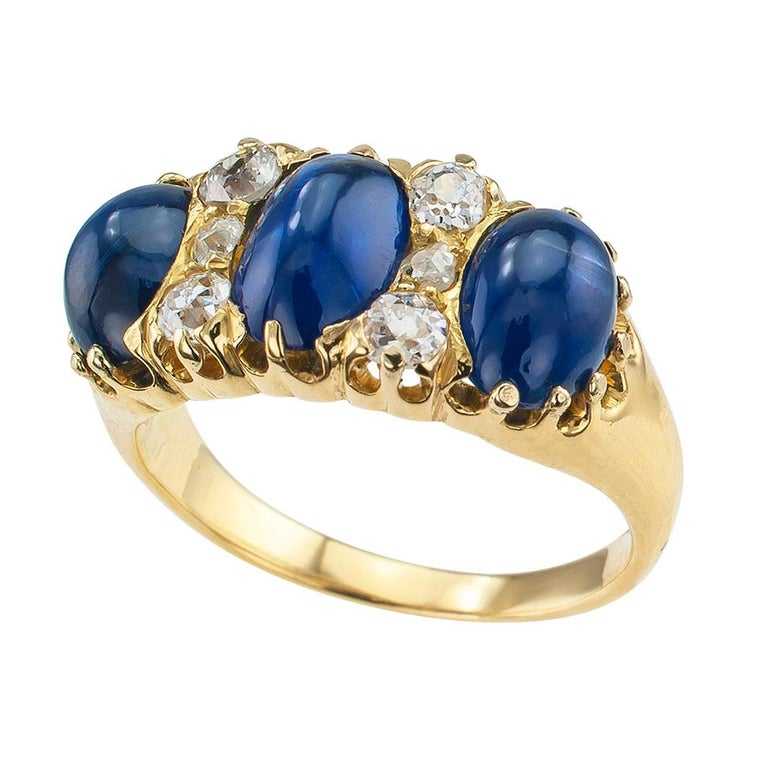 Victorian three-stone cabochon sapphire diamond and gold ring circa 1900. DETAILS: Lady's Victorian cabochon blue sapphire diamond and gold ring. Three oval cabochon sapphires together weighing approximately 3.50 carats. Six round old-cut diamonds