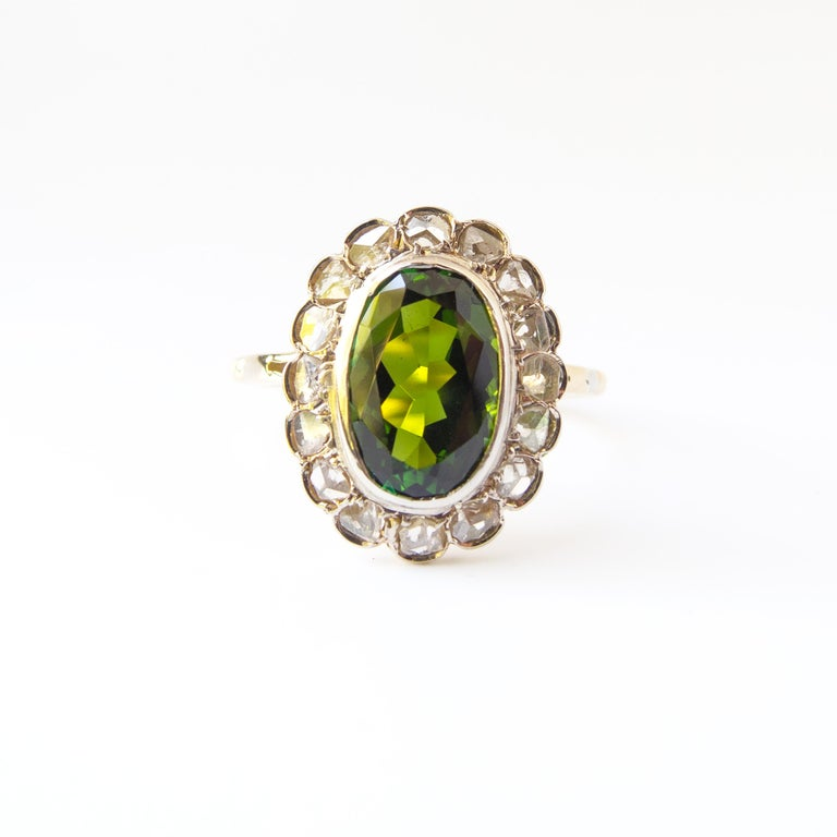 Sixteen rose-cut diamonds encircle a deep, glittering and complex tourmaline just over 2 carats in size that is simultaneously emerald and forest green. That's one thing I love about tourmaline: it's a pleochroic gemstone, meaning it displays