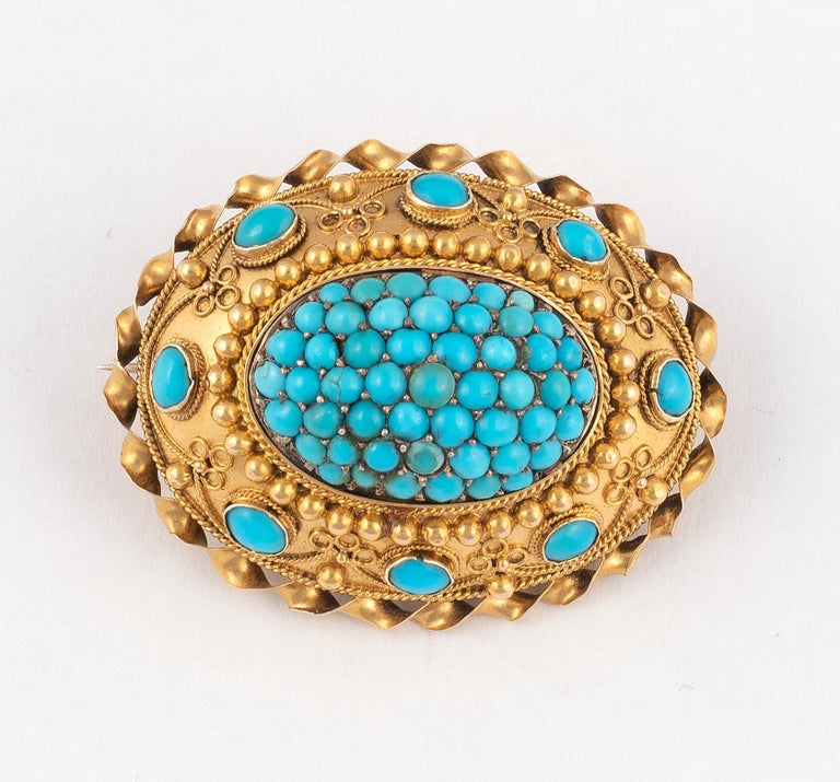 The brooch of oval form, set with a cluster of circular cabochon-cut turquoises, the surround with wirework detailing and further oval cabochon-cut turquoises, with glazed compartment to the reverse. Brooch width 36mm