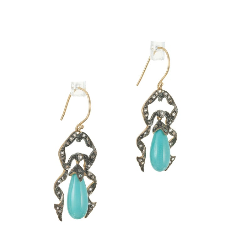 Victorian Revival Turquoise and diamond dangle earrings. 9k yellow gold ribbon style frames with 60 round diamonds and two pear shaped turquoise dangles.   15 x 7mm pear Turquoise 60 round diamonds, approx. total weight .40cts, H to I, SI1 - I 5.9