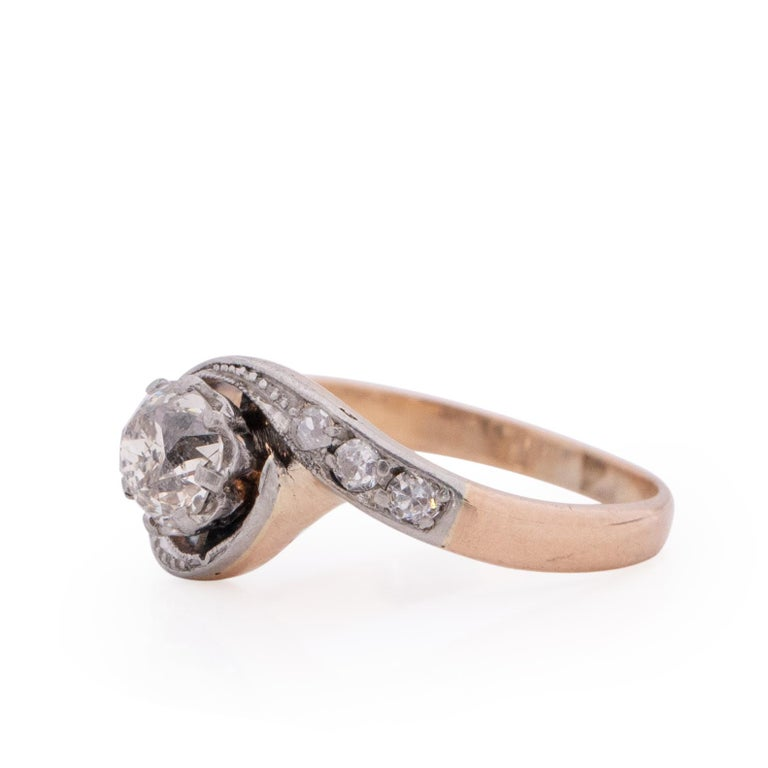 This is a classic example of a Victorian ring. Sitting the the two tone platinum and rose gold setting is a beautiful chunky old mine cut diamond. encompassing the center diamond is the winding shanks of the ring, in the platinum is six beautiful