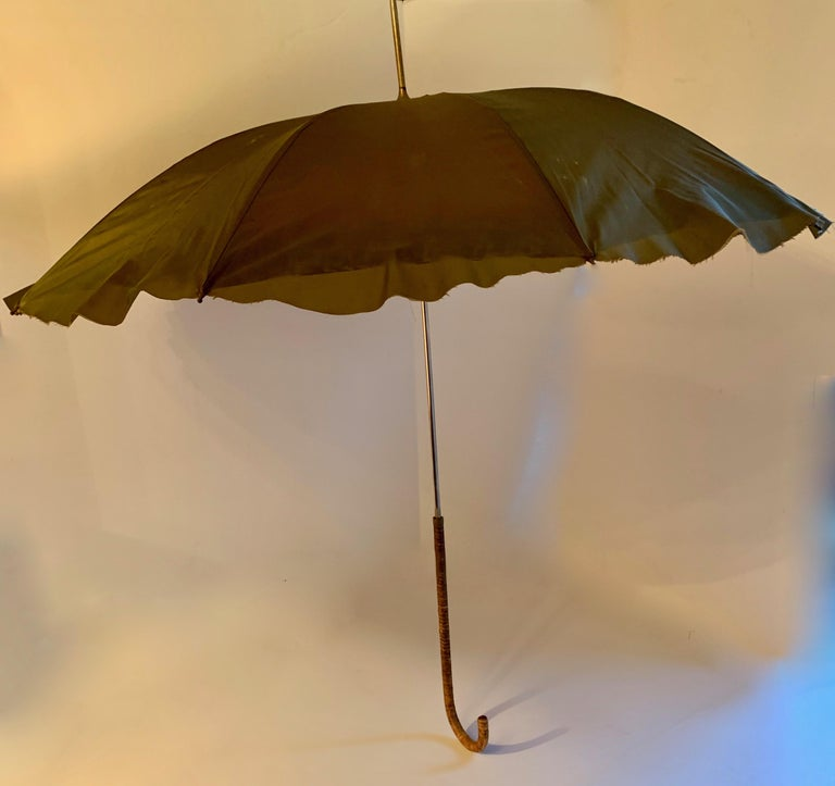 Victorian umbrella with cane handle - a unique and handsome piece, the umbrella is held in place with a 'snake' band. When open, the fabric is a melange of color and texture, with a raw edge. The handle is a beautiful woven cane... Very good vintage