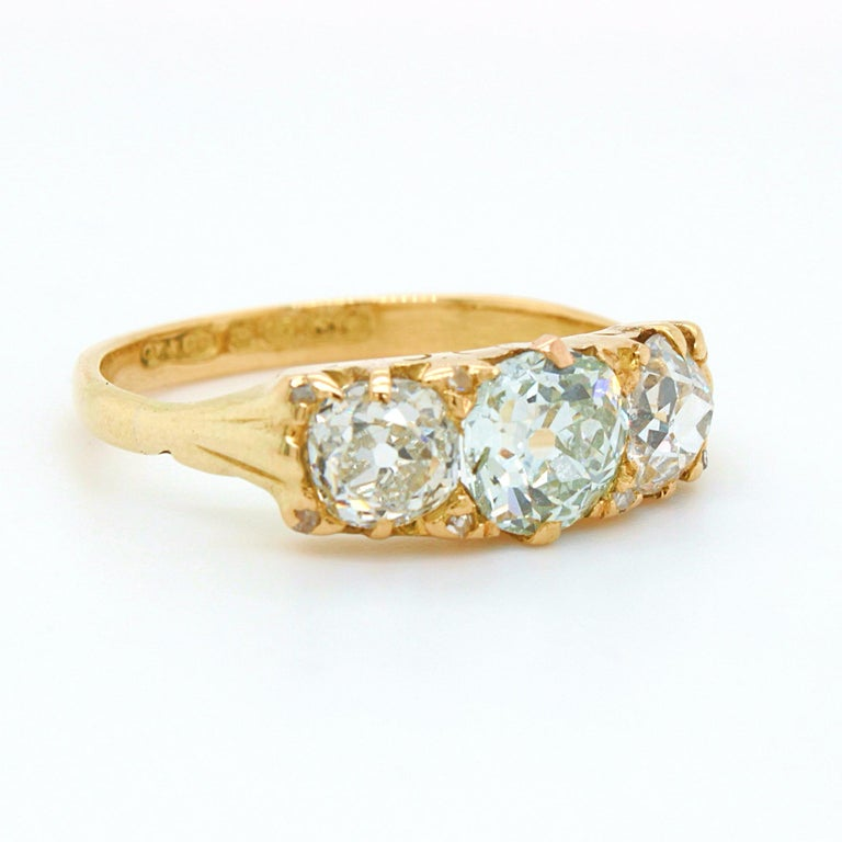 A Victorian three diamond ring in 18k yellow gold, ca. 1880s. The bigger centre stone out of the three is a very light green old European cut diamond weighing 0.88ct, accompanied by a GIA certificate, with no eye visible inclusions. The two side