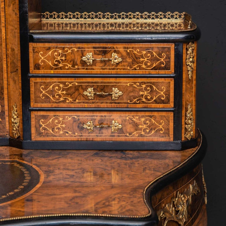 A beautiful walnut ladies writing desk from the mid Victorian period. Very shapely and decorative, with ormolu mounts and mouldings throughout combined with boxwood inlays and stringing. Recently repolished and with a new leather writing surface,