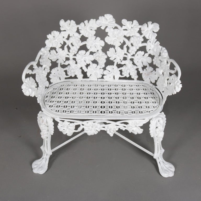 Victorian reticulated garden bench features cast iron construction in grape and leaf pattern and seated on cabriole legs terminating in stylized paw feet garden table, painted white, 20th century.   Measures: 27