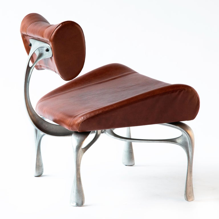 """New deep cognac leather victory lounge chair: leather and burnished cast magnesium-aluminum alloy, made in Chicago, 2012/2016. A 2019 variation on the lounge chairs created for Victory at the Meadowlands in 2012-13. It is about 31"""" wide x 33.5"""" tall"""