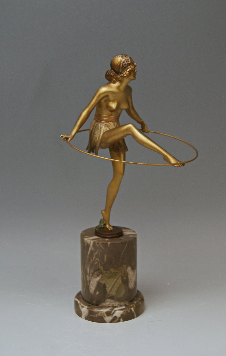 Interesting Vienna bronze figurine: Semi-nude lady holding a hoop   It is a finest figurine. The bare-breasted lady stands on round flat bronze base which is attached to column made of brownish-white marble. The female nude holds a hoop in both