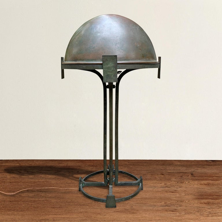 An incredible fine quality early 20th century Vienna secession bronze table lamp with a removable dome shade supported by four square uprights turning into legs with spade-form feet and a circular base. The bronze has patinated beautifully! Marked